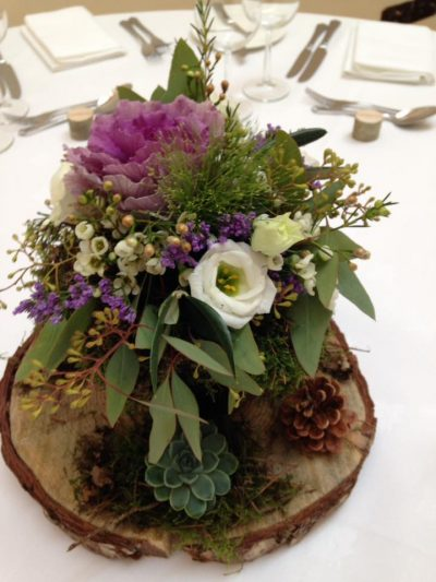 Rustic table centres log pine cones ornamental cabbage succulents